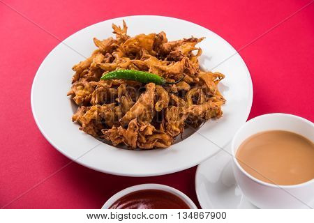 Crispy onion bhaji or kanda bhaji or fried onion pakore or pakode, delicious street food, favourite indian snack in monsoon served with hot tea