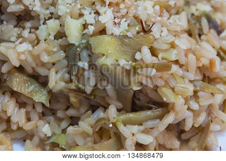 Brown rice with carciofi and grated cheese on the plate close-up.