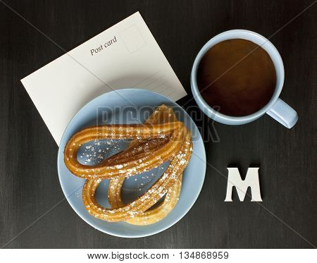 Plate of churros traditional Spanish (and especially Madrid) dessert (especially for Sunday breakfast) with cup of hot chocolate with blank postcard with copyspace and letter 'M' on dark tabletop