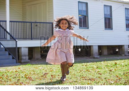 Toddler kid girl running in park with flowers dress latin ethnicity