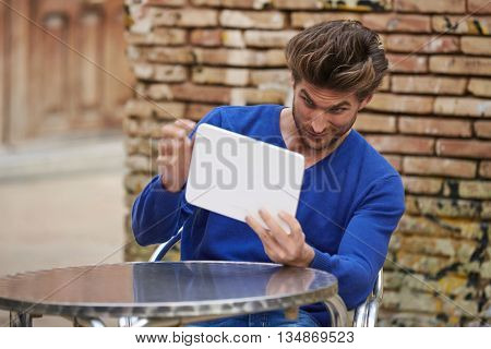 Young man using tablet pc as a mirror to fix his hair in outdoor cafe