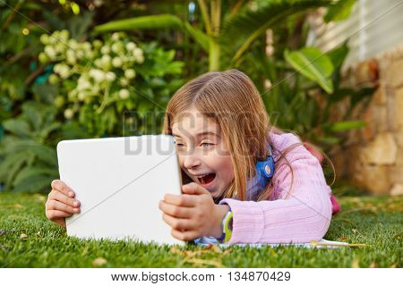 Blond kid girl with tablet pc lying on grass turf smiling