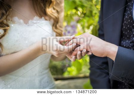 Unrecognizable couple of newly-married wearing wedding rings