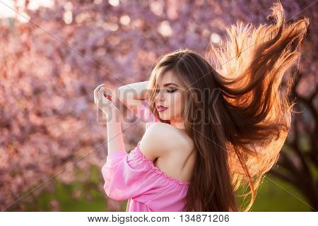 Beauty Girl Outdoors enjoying nature. Beautiful Teenage Model girl with long healthy blowing hair running in blossom park, Sun Light. Glow Sun. Free Happy Woman.