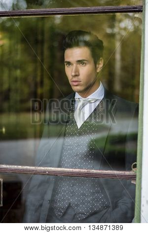 Handsome young man or bridegroom looking through the window