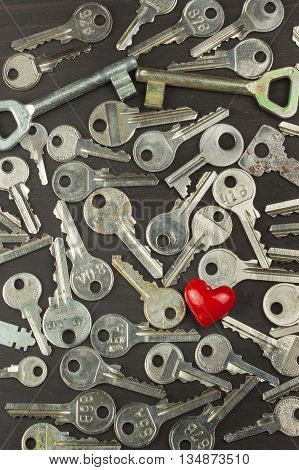 Silver keys on a dark wooden board. Different types of keys. Key to the heart. Symbol of love.