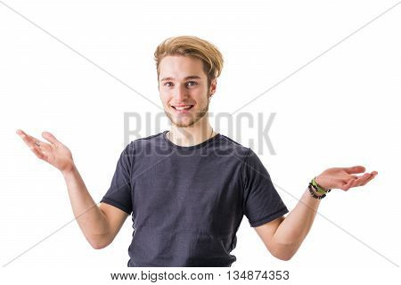 Confused young blond man widened arms while looking at camera. Isolated on white background