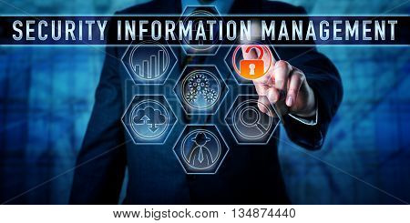 Male corporate manager is pressing the industry term SECURITY INFORMATION MANAGEMENT on an interactive touch screen interface. Business metaphor and data security concept. Abbreviated as SIM.