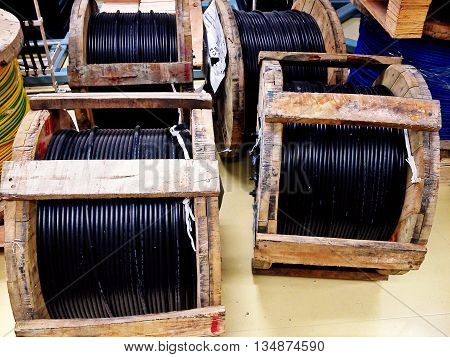 Wooden coil of electric and Fiber optic cable in a warehouse .