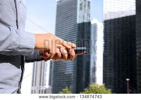 Businessman holding and using the mobile smart phone outside