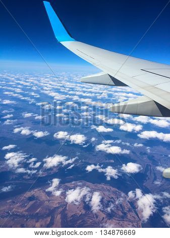 Aircraft wing flying over clouds, Aircraft wing on cloudscape and blue sky