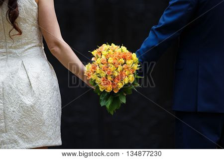 Hands of newlyweds holding the bridal bouquet on a black background