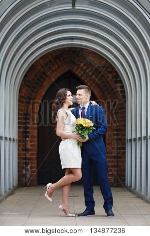 Romantic wedding couple embracing in the arch