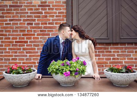 Romantic wedding couple kissing on a background of brick wall