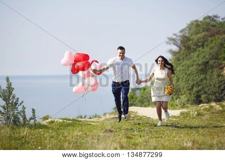 Happy wedding couple running with red air-balloons