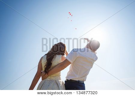 Romantic wedding couple looks at the sky and watchs go the flying air-balloons