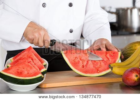 Chef cutting a delicious sweet a watermelon
