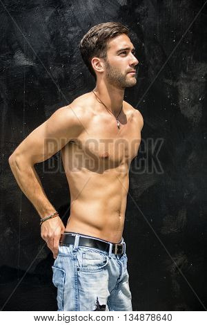 Handsome unshaven shirtless young man standing against black wall, looking to a side