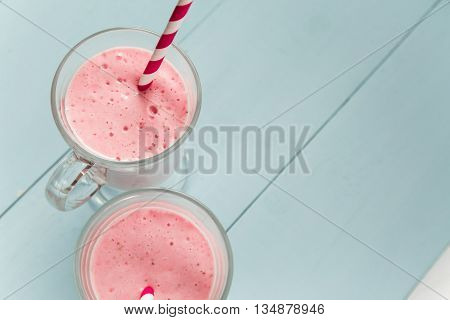 Two milk shakes with strawberries ice-cream pink cocktail with straws on blue wooden table copy space at right top view
