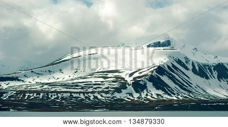 Clouds over mountains covered with snow in the cold arctic environment in Svalbard.