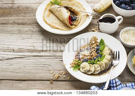 Healthy breakfast trend. Thin oat pancakes with banana, blueberries, goji berries, sesame and chia seeds with chocolate cream and fresh cream portions served with honey, mint and peanuts. selective focus