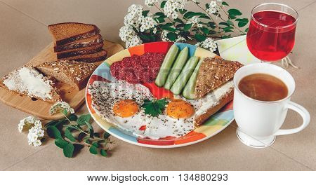 Delicious Tasty Breakfast from Eggs,Bread with Butter,Sausage on the Colorfull Plate.CoffeeRed Juice with White Flowers.Brown Background.