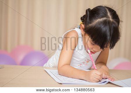happy schoolgirl works on her homework write something in her notepad