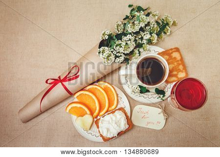 Romantic Birthday Breakfast.Cup of CoffeeGlass og red BeverageCut OrangeBiscuit with Cottage Cheese.Wish Card with Flowers.Top View