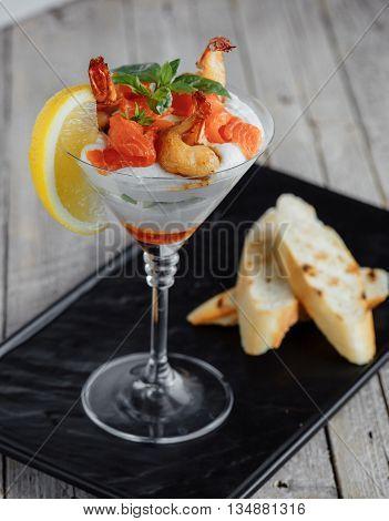 Salad shrimp cocktail sauce with salmon lemon and basil on a wooden table