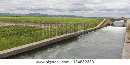 Huge irrigation canal flows over the fertile meadows of High Guadiana or Vegas Altas Extremadura Spain. Panoramic shot