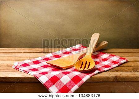 Kitchen utensils on tablecloth on wooden table over grunge background