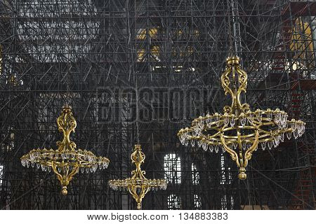 Gold color, ancient chandeliers with scaffolding in the background.