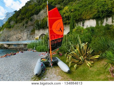 Torbole, Italy - September 21, 2014: Lake Garda beach with tourists and catamaran Smartkat in Torbole, Italy. Torbole is one of the most popular towns on Garda Lake, known as a wind surfers paradise.