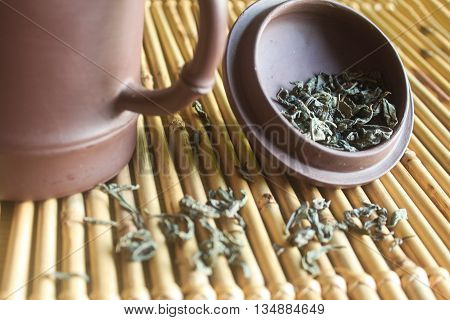 Green tea is scattered on textured bamboo napkin, standing next to a cup