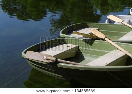 horizontal perspective view of many recreational boats on a lake with their oars up