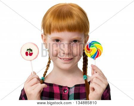Little attractive redheaded girl with freckles holding colorful candy in the hands. Close-up isolated on white background.