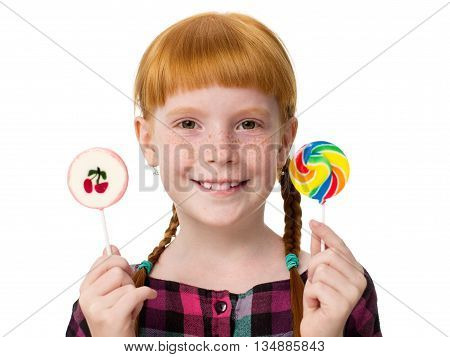 Little redheaded girl with freckles holding colored candies in hands and smiling