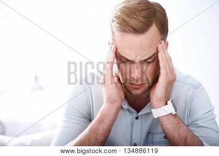 How can I cure it. Pleasant moody sick man touching his temples and having a headache while sitting on the couch