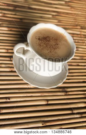 White cup of coffee stands on a textured napkin