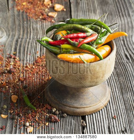 Coloured bright hot peppers, bell pepper, chili powder in a metal vintage cups and saucers on a dark wooden background. selective focus