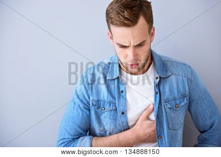 Measure the heartbeat. Handsome pleasant gloomy man holding his hand on the heart and feeling ache while standing isolated on white