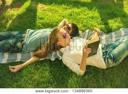 Little teenage boy and girl are lying on grass girl reads book and boy wears earphones chillout