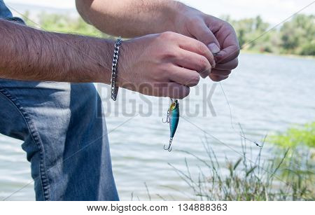 Man prepares his spinning for fishing and puts bait with hook on