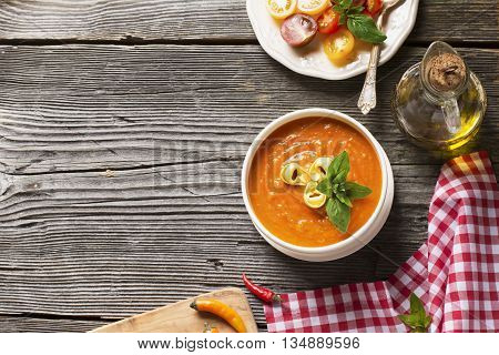 Fragrant homemade tomato soup puree with tagliatelle on a dark wooden background with bright colored mini tomatoes, hot pepper, olive oil decanter and a napkin in a red white checkered. selective focus