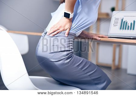 Pain after hard working day. Pleasant sick woman sitting at the table and holding her hand on the back while feeling a terrible ache