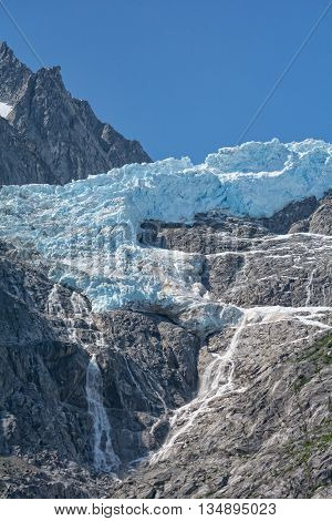 A glacier clings to a vertical rock face and is melting in the heat of the day.
