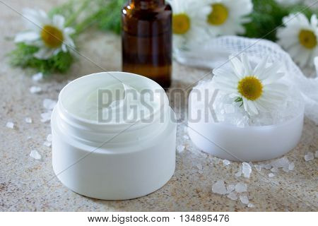 Face Cream With Chamomile Essential Oil Bottle Of Aromatherapy And Salt On Brown Stone Background. S