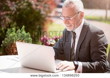 That is a good day. Positive handsome smiling senior businessman sitting at the table outside and using laptop while feeling glad