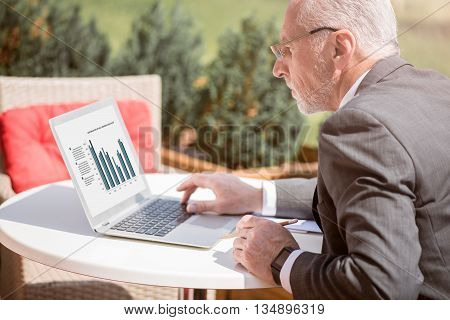 Much work to do. Pleasant concentrated senior businessman sitting at the table and using laptop while staring at the screen