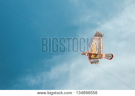 Bird shaped kite flying in blue sky with white clouds. Concept of freedom